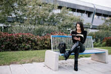 Stylish Female Entrepreneur Sitting On Bench And Taking Notes In Organizer While Working In Urban Park