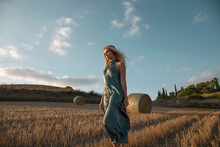 Peaceful Female In Elegant Dress Standing On Dry Field In Rural Area And Looking Away