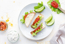 Small Delicious Tacos With Red Caviar And Green Lettuce Served On Wooden Cutting Board On Table