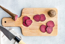 Top View Composition Of Ripe Raw Beetroot Slices Placed On Wooden Cutting Board On Kitchen Table Near Sharp Knife