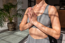 Crop Unrecognizable Female With Prayer Hands Meditating In Room With Sunlight While Practicing Yoga At Home