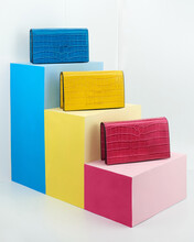 Colorful Modern Leather Handbags On Color Steps In Studio Against Gray Background