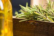 Rosemary Sprigs With Green Leaves Placed In Small Wooden Chest Near Glass Bottle With Oil On Surface In Light Place