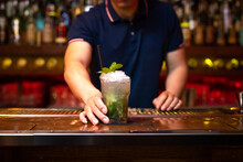 Hand Of Unrecognizable Bartender Gives You A Well Elaborated Mojito Cocktail In The Bar After He Finished To Prepare It
