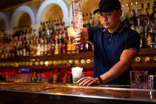 Young Asian Bartender Pouring Rum In The Glass While Preparing Mojito Cocktail In The Bar