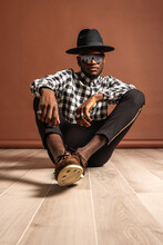 Young Cool African American Male Model In Checkered Shirt And Hat Looking At Camera While Sitting On Brown Background