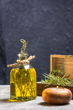 Glass Bottle Of Essential Oil With Rosemary Twigs And Burning Organic Wooden Candle On Gray Table