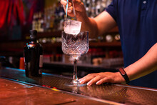 Unrecognizable Bartender Putting A Big Ice Cube Into The Glass While Preparing A Gin Tonic Cocktail In The Bar