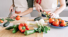 Crop Unrecognizable Homosexual Girlfriends Cutting Cucumber While Preparing Healthy Vegetarian Food At Table In House