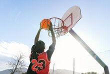 From Below Of African American Male Streetball Player In Moment Of Jumping And Scoring Basketball In Hoop