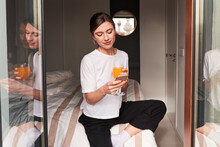 Content Young Lady In Casual Clothes Drinking Fresh Orange Juice And Messaging On Smartphone While Resting On Bed In Daylight