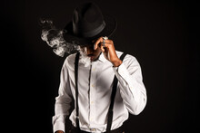 Masculine African American Male In White Shirt And Hat Exhaling Vapor While Smoking E Cigarette