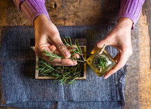 Top View Of Crop Unrecognizable Female Demonstrating Small Wooden Chest Filled With Herbs Twigs With Green Leaves Near Essential Oil Glass Bottles On Textile Near Scissors At Table