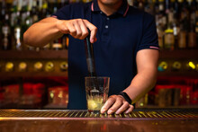 Unrecognizable Bartender Crushing Lemon Wedges In The Glass While Preparing Mojito Cocktail In The Bar