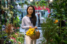 Beautiful Asian Girl Buying Flowers In Flower Shop While Carrying A Wicker Basket With Yellow Flowers.