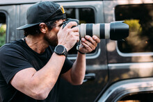 Side View Of An Adventurous Photographer Taking Photos Next To His Off-road Car