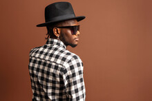 Young Cool African American Male Model In Checkered Shirt, Hat And Sunglasses While Standing On Brown Background