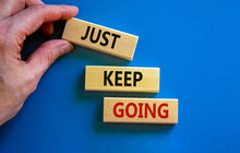 Just Keep Going Symbol. Wooden Blocks With Words 'Just Keep Going'. Beautiful Blue Background, Businessman Hand. Business, Just Keep Going Concept, Copy Space.