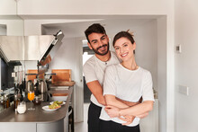 Side View Of Young Romantic Ethnic Guy In White T Shirt Smiling And Hugging Happy Girlfriend While Looking At Camera