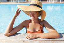 Beautiful Happy Woman In Hat Relaxing In Water At Pool Wooden Pier, Enjoying Summer Vacation At Tropical Resort. Portrait Of Smiling Young Female Sunbathing At Swimming Pool Edge. Travel