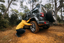 Side View Of An Adventurer Checking The Pressure Of The Wheels Of His Off-road Car In The Mountains