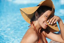 Beautiful Happy Carefree Woman In Hat Relaxing In Pool, Enjoying Summer Vacation. Portrait Of Smiling Young Female Sunbathing And Resting At Swimming Pool At Tropical Resort. Holidays And Travel