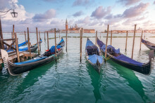 Traditional Gondolas Moored On Rippling Water Surface On Background Of City And Sundown Sky In Venice
