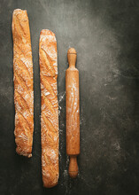 Top View Composition With Two Artisan Bread Loaves Placed Near Wooden Rolling Pin On Black Background