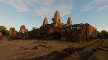 Aged Stone Temple Complex Exterior Against Lawn Under Blue Sky In Cambodia In Evening