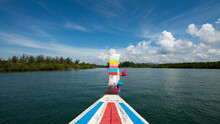 Aged Boat With Striped Ornament On River Against Trees Under Blue Sky With Cumulus Clouds In Thailand