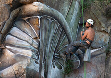 Side View Full Body Of Painter With Spray Paint Making Graffiti Hanging On Rope On Steep Rocky Slope