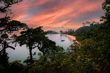 Spectacular View Of Ocean With Boat Against Lush Green Trees Under Sky With Fluffy Clouds At Sunset In Thailand