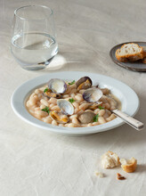 Appetizing Traditional Spanish Stewed White Fabes Beans With Mollusks In Plate With Fresh Parsley Leaves On Tablecloth