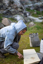 Side View Male Artist Turning Page Of Album With Sketches In Nature