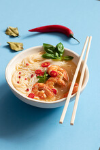 Tom Yum Soup In Bowl With Chopsticks On Blue Background