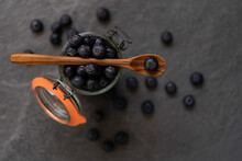 Fresh Blueberries Falling In Glass Jar And Splashing Water On Gray Background In Studio
