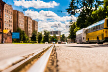 Summer In The City, The Street With Tramway Rails And Parked Buses. Close Up View Of A Tram Rail Level