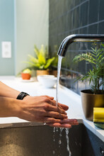 Crop Unrecognizable Female Washing Hands Under Pure Water Flow From Tap In House Kitchen