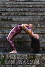 Side View Of Flexible Female In Sportswear Doing Backbend And Practicing Yoga With Namaste Gesture And Closed Eyes While Balancing On Stone Steps