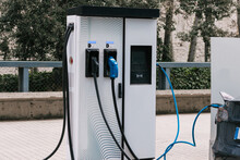 Modern Alternative Energy Electric Car Connected To Charging Station With Plug Of Power Cable Supply On Urban Street