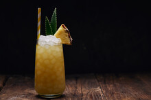 Wooden Table With Glass Of Yellow Cocktail With Ice Cubes And Refreshing Cocktail Garnished With Spiky Leaves And Striped Straw