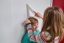 Sister Helping Brother With Measuring Him Height With Ruler And Pencil Near Wall
