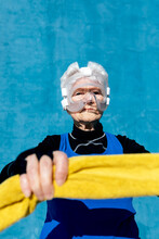 Serious Mature Female In Activewear In Protective Boxing Head Guard With Towel In The Hands Standing On Blue Background And Looking At Camera