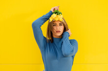 Young Female In Casual Wear With Makeup And Blossoming Yellow Flower Sprigs Looking At Camera