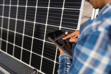 Cropped Unrecognizable Ethnic Male Technician In Checkered Shirt Browsing Tablet While Standing Near Photovoltaic Panel Located In Modern Solar Power Farm