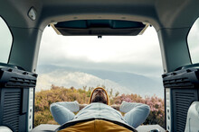 Young Male Camper In Outerwear Lying Down On Van With Eyes Closed Enjoying Scenic View Of Highlands