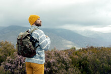 Back View Of Thoughtful Male Camper With Warm Hat Standing With Backpack In Highlands Admiring And Enjoying Picturesque Views