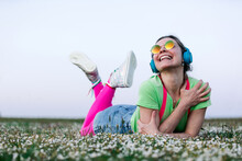 Delighted Young Female In Colorful Clothes Listening To Favorite Music Via Headphones While Lying On Grassy Meadow With Legs Crossed And Looking Away Happily