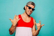 Rebel Young Ethnic Hipster Man In Cap And Black Sunglasses With Tongue Out Showing Sign Of Horns While Standing Against Blue Background