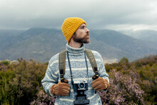 Thoughtful Male Camper With Warm Hat Standing With Photo Camera And Backpack In Highlands Admiring And Enjoying Picturesque Views